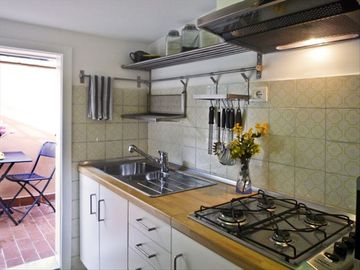 Kitchen opens out to the terrace. It is fully equipped with pots, pans, dishes.