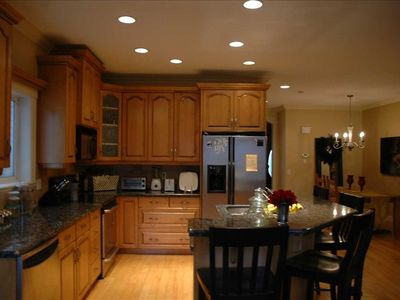 Full upscale kitchen with breakfast bar, spices and assorted appliances