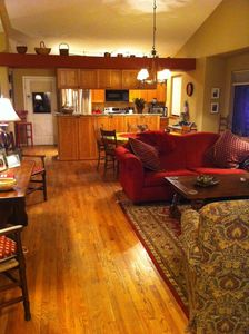 Living room through to kitchen. Nice hardwoods, beautiful furnishings.