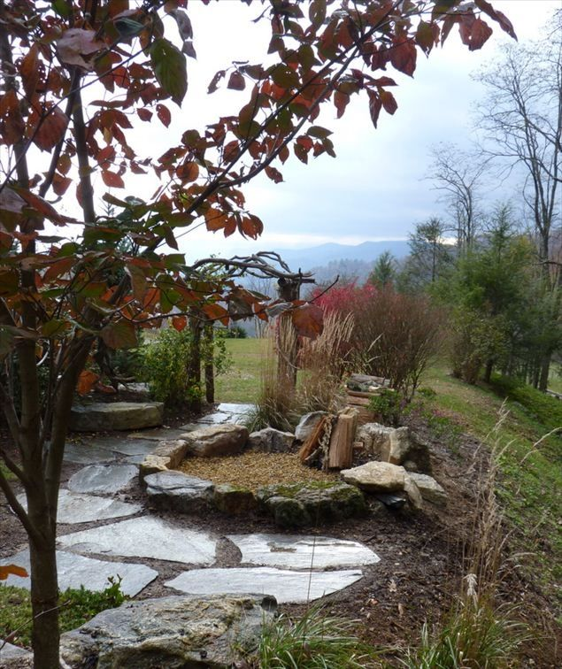 Outdoor firepit situated above stream and overlooking garden and mountain range.