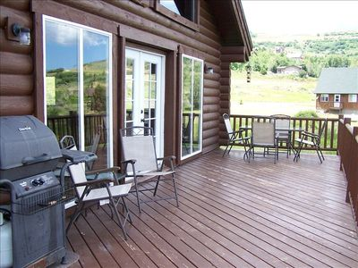 Large l-shaped deck has beautiful lake view with BBQ grill, tables, & chairs