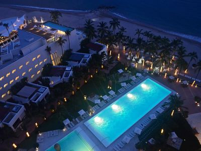 view of the pool area from beachfront terrace at sunset