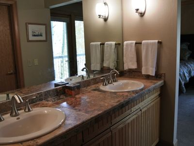 Roomy master dressing area has double sinks and walk in cedar closet.