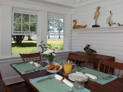 Breakfast room has windows on three side with expansive water views.