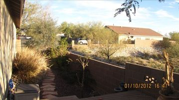 Landscaped side yard overlooking dry wash and neighbor's home