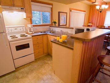 Fully-equipped open kitchen with fridge, stove, microwave, coffee maker, etc.