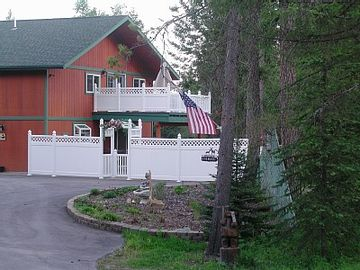 Whitefish house rental - Front view of house, large pebble deck beyond fence.