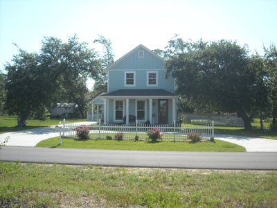 Cottage is surrounded by open area and circled by live oaks