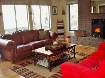 Flagstaff house rental - Enjoy the woodstove while taking in the private woods view from the couch.