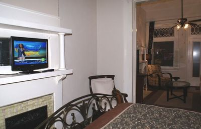 House Bdrm #1 also features flat screen TV, elegant chair, dresser & mirror