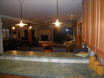 view from kitchen, looking over bar countertop into the large dining/family room
