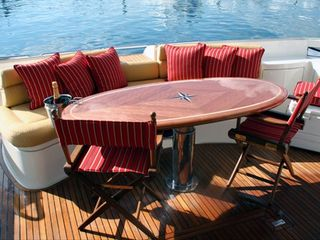 Aventura yacht photo - covered Deck outside wood table with teak floor finish