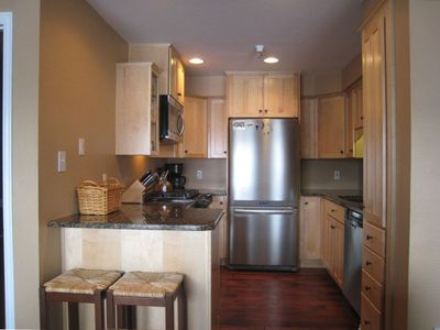 Remodeled kitchen with gas range, granite countertops & stainless appliances