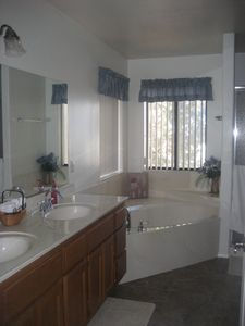 Master bathroom - large jetted tub with view, shower stall at right.
