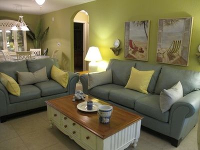 Living Room with new ocean blue leather sofa and love seat adjacent to lanai.