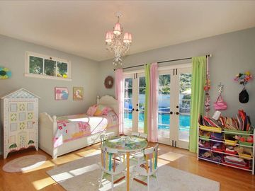 Girls bedroom has twin bed with twin pull out trundle and french doors to patio