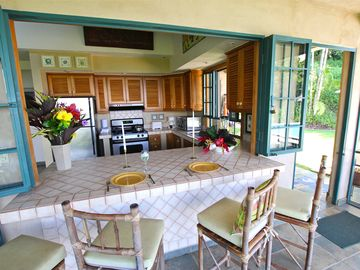 Fully equipped kitchen with breakfast bar over looking the pool and Ocean views