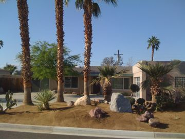 Attractive desert landscaping and an attractive glass/metal garage door.