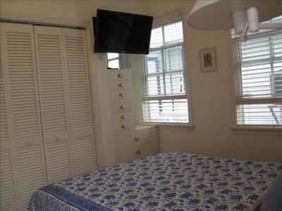 wide screen TV in bedroom, chest of drawers, washer and dryer
