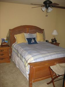 Nautical themed queen guest bedroom with flat screen tv and alder wood doors