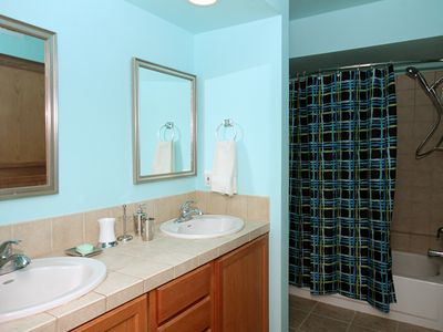 Bathroom with dual sinks and tile counters; hand-held shower attachment