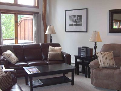 Big Sky condo rental - Another View of the Great Room with Window to Deck and Pine Trees