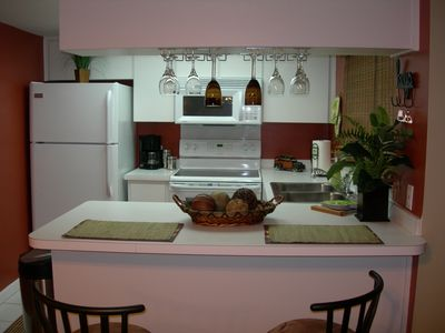 Kitchen with ceramic top range, microwave, deep scrub dishwasher, breakfast bar