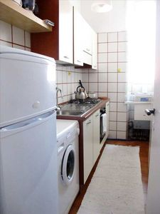 A fully equipped  kitchen with a four burners stove and washing machine