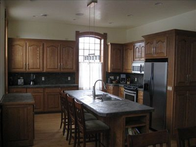 Gourmet kitchen features custom cabinets and stainless steel appliances,