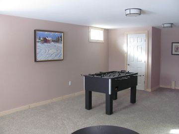 Lower level family room with fooseball table and full sleeper sofa.