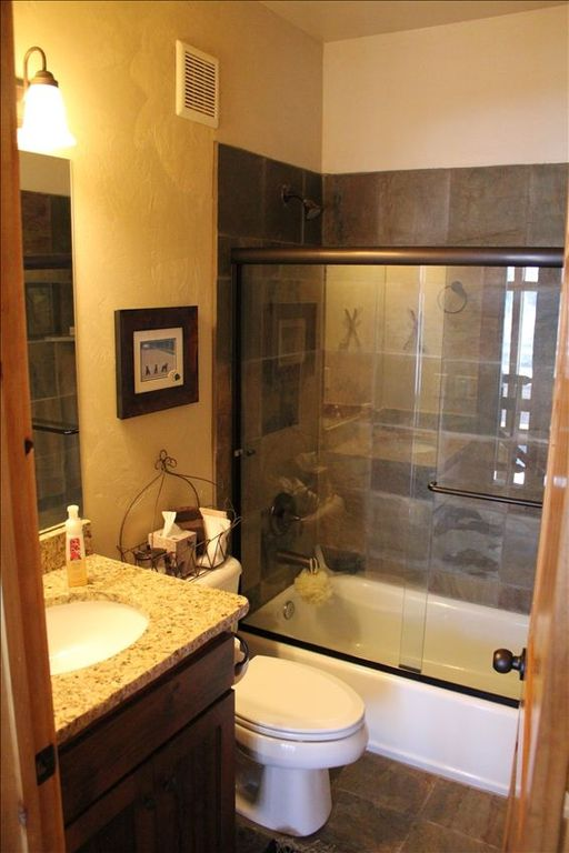 Loft bathroom with full shower/bathtub, granite countertops, and slate tile