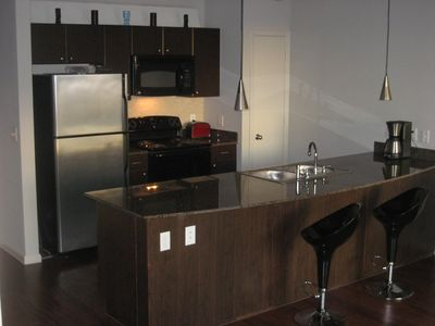 Large, fully stocked modern kitchen with Stainless appliances and bar seating