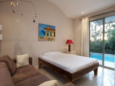 Guest bedroom with double bed and view of pool