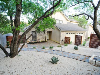 New xeriscaped yard with lit pathway to front courtyard and entry door