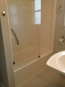 Glass panel step in shower, tile floor, white pedestal sink, downstairs bathroom