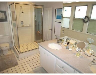 Master bathroom with glass shower, double sink, and ocean views.