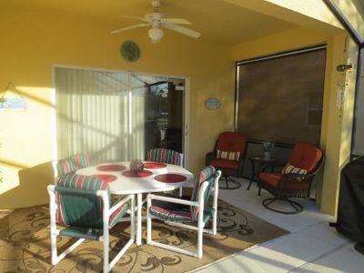 Lanai area with dining table seating 8 and a cozy wicker bistro set for two.