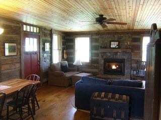View of the living / dining room featuring gas fireplace and antique logs.