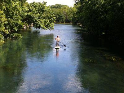 Paddle boarder enjoying a peaceful Sunday morning on the river.