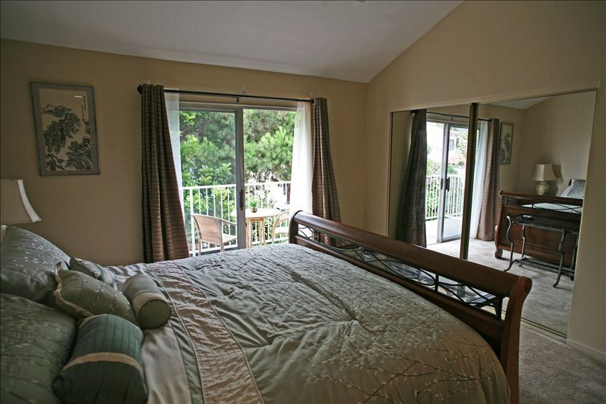 Large master suite with private balcony surrounded by mature trees.