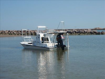 Our flats boat at the gulf landing beach at Padre Island, jetty at back