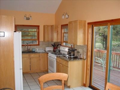 Clean functional kitchen with granite counters and propane gas stove