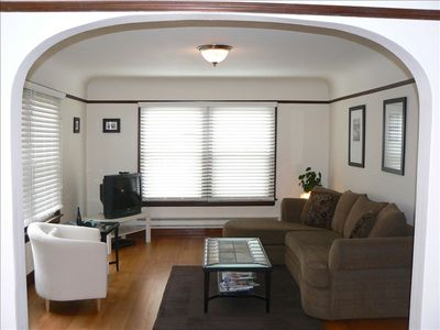 Beautiful living room with large windows, cove ceilings, hardwood floors, and TV