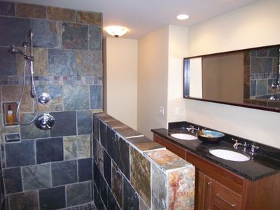 Upper level slate tiled bath with granite countertop.