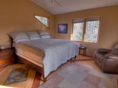 Plush King size bed in master bedroom, windows look out to Mt Alyeska