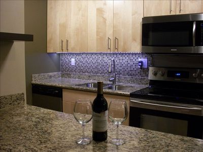 Custom Kitchen with Granite Countertops, Stainless Appliances, and Glass Tile.