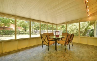 Inviting screened-in porch overlooks backyard. Great place for coffee and a book