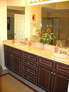 Elegant master vanity with double sinks,  marble countertops and separate shower