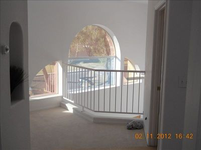 View out of master bedroom double doors onto landing overlooking living room.
