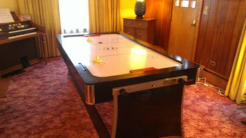 Air hockey/pool table in living room & organ